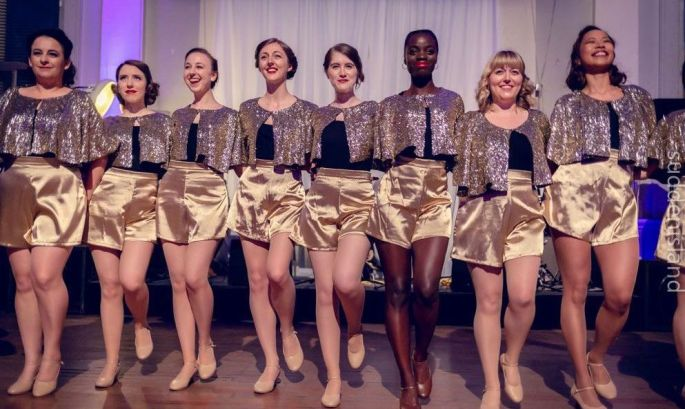 The London Starlings in gold capes and gold shorts smiling and standing in a line with hands behind each other's backs